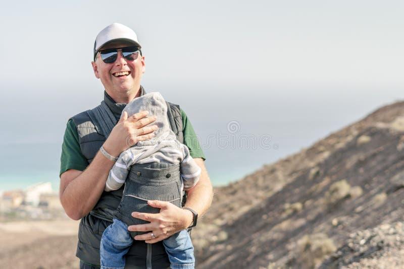 Padre con i suoi 9 mesi di figlio in marsupio sulla traccia immagini stock