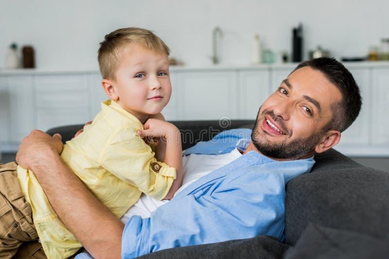 padre con il piccolo figlio sveglio che si trova sul sofà e sul sorridere fotografia stock libera da diritti