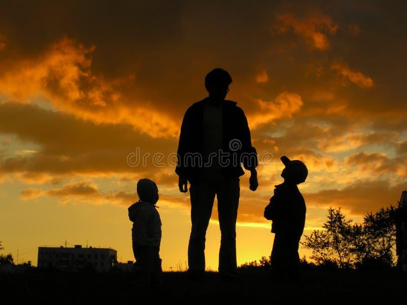 Padre con il tramonto 2 dei bambini fotografia stock