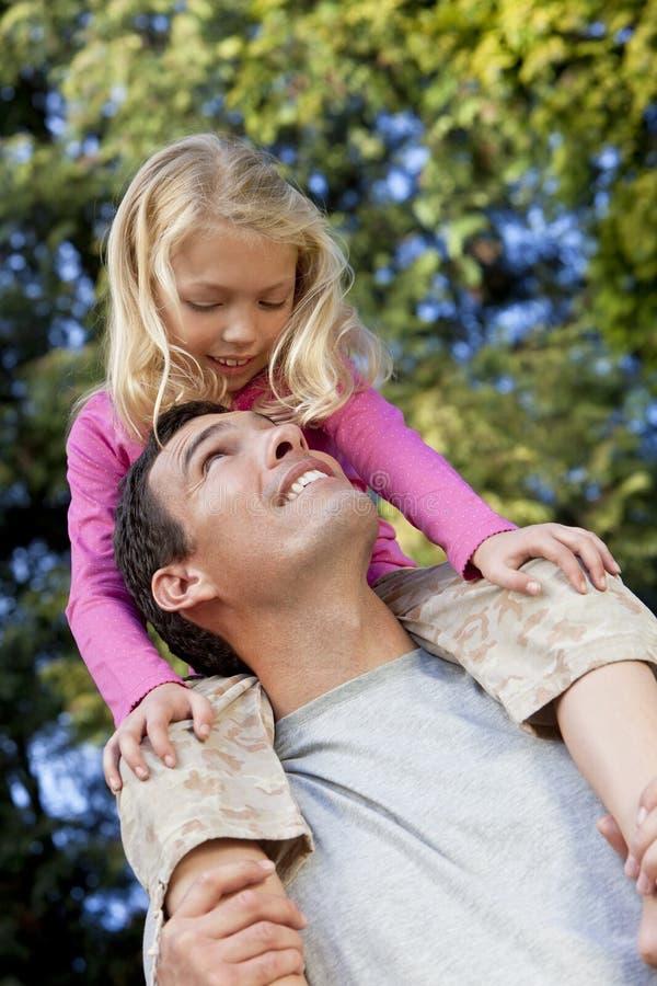 Padre con la hija en los hombros que se divierten imagenes de archivo