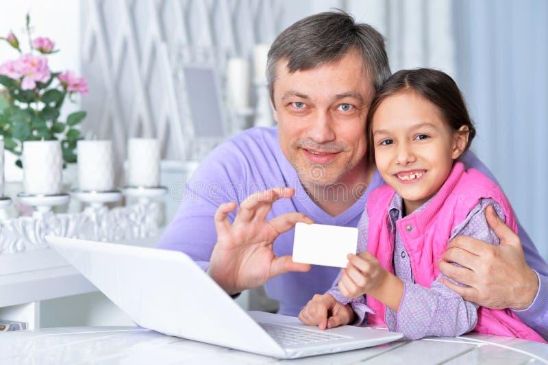 Padre con la pequeña hija usando el ordenador portátil que hace compras en línea imagenes de archivo