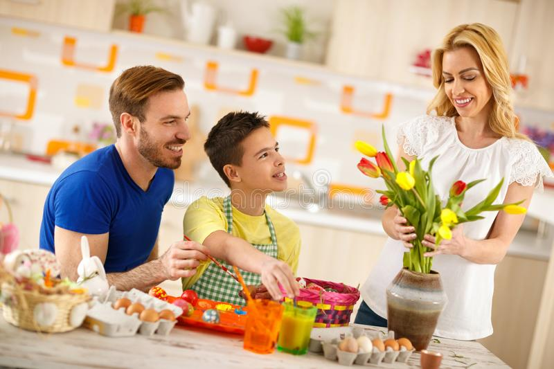 Padre con los huevos que colorean del hijo mientras que la madre arregla tulipanes en florero foto de archivo