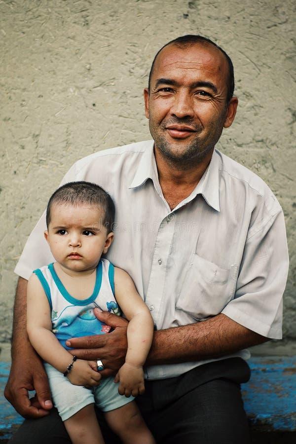 Padre con los niños en el frente las paredes típicas del fango del desierto imagenes de archivo
