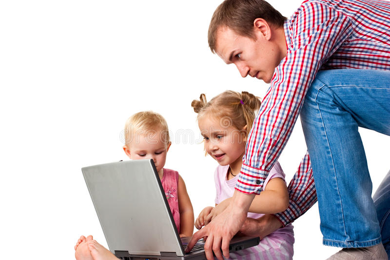 Padre con los niños que juegan en la computadora portátil foto de archivo libre de regalías