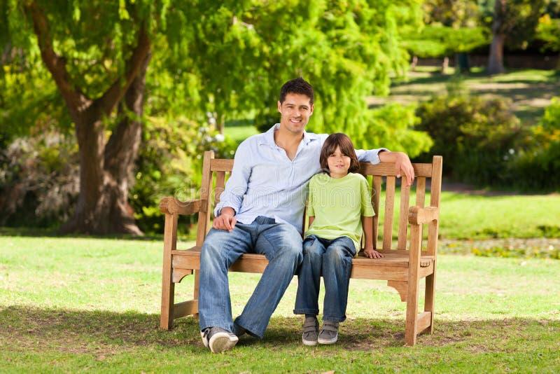 Padre con su hijo en el banco fotos de archivo