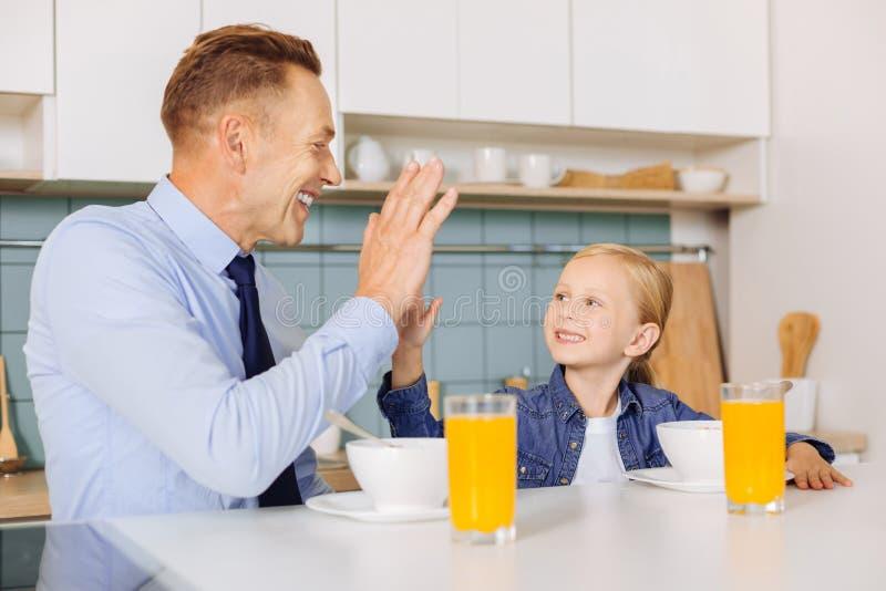 Padre contentissimo allegro e figlia che si danno livello cinque fotografie stock libere da diritti