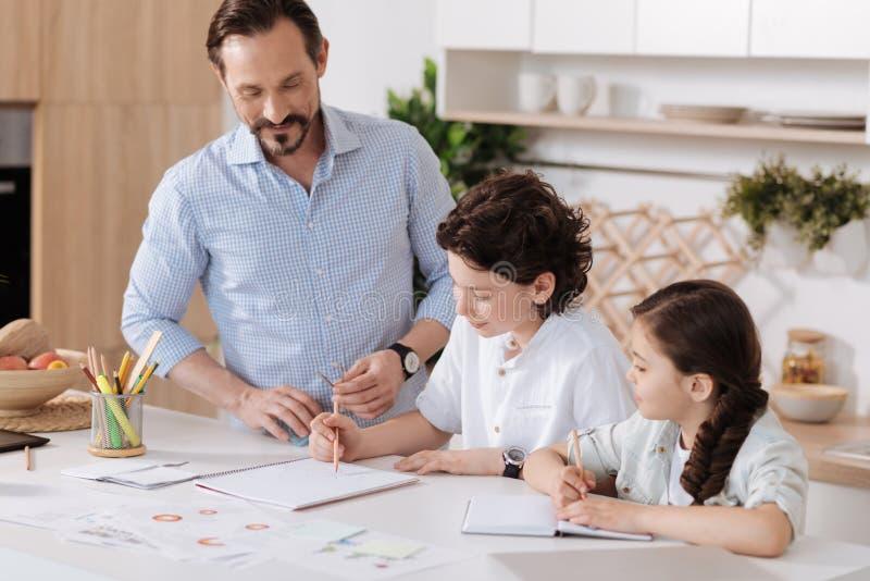 Padre contento que mira a su hijo el hacer de sumas fotografía de archivo libre de regalías