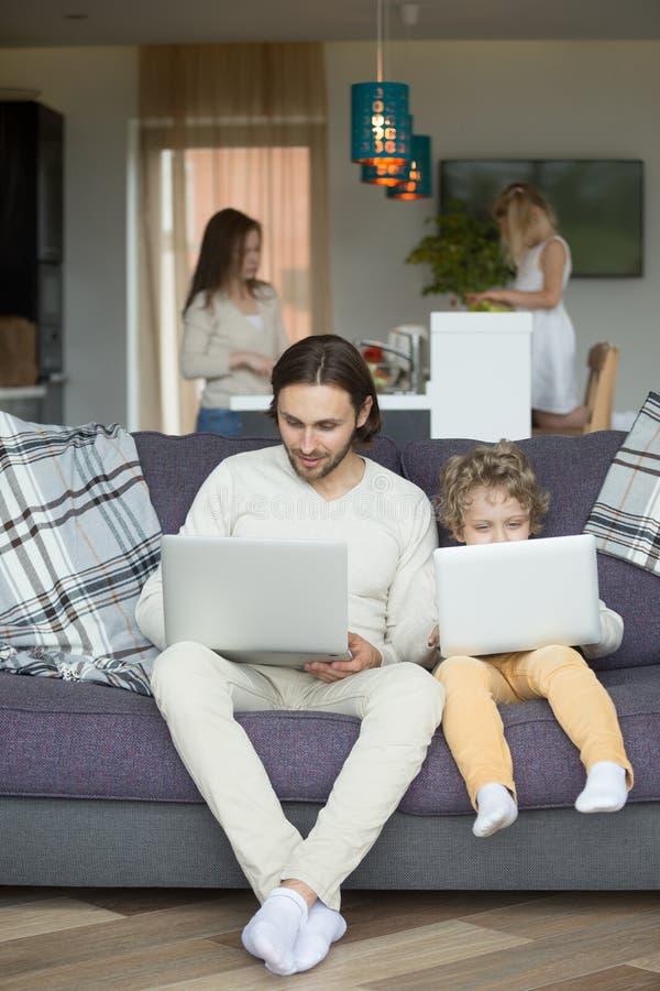 Padre d'imitazione del figlio che si siede sul computer portatile della tenuta dello strato a casa fotografia stock