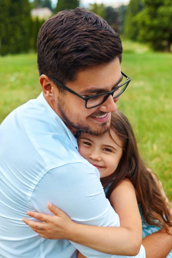 Padre And Daughter Hugging en parque Familia que abraza al aire libre imagen de archivo libre de regalías