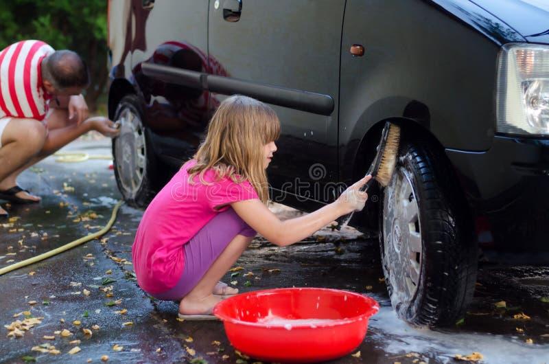 Padre de ayuda de la hija feliz para lavar el coche foto de archivo