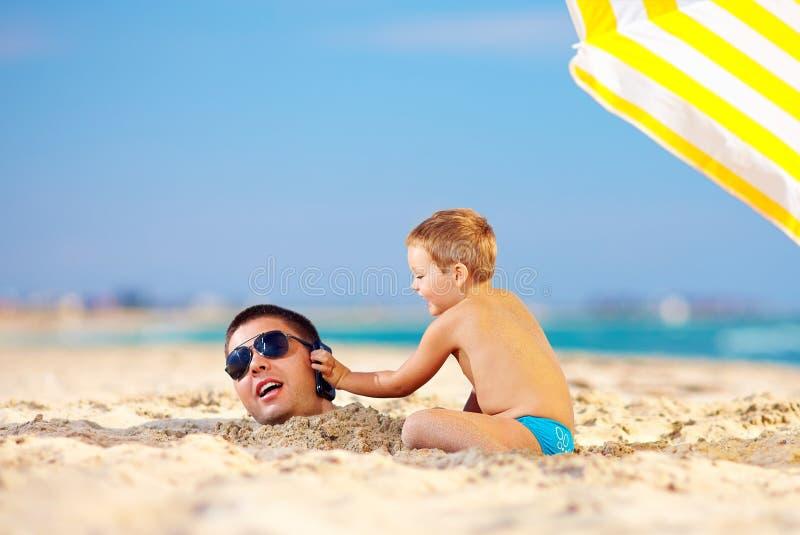 Padre de ayuda del niño feliz hablar en el teléfono en arena fotos de archivo libres de regalías