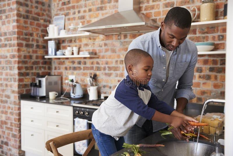 Padre de ayuda To Prepare Vegetables del hijo para la comida en cocina fotos de archivo libres de regalías