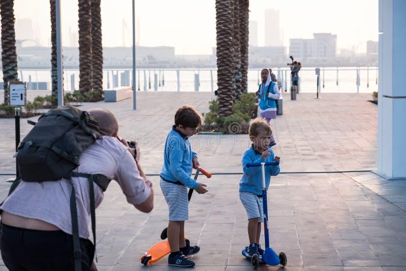 Padre de dos imágenes que toman de sus hijos en la lumbrera Abu Dhabi imagen de archivo libre de regalías