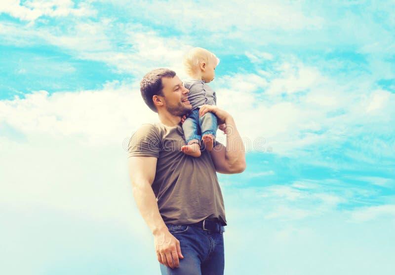 Padre de la foto atmosférica de la forma de vida y niño felices del hijo al aire libre sobre el cielo azul imagen de archivo libre de regalías