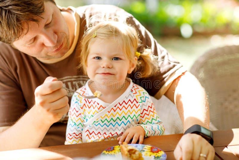 Padre de mediana edad joven que alimenta a la pequeña niña pequeña linda en restaurante Niño adorable del bebé que aprende la con imágenes de archivo libres de regalías