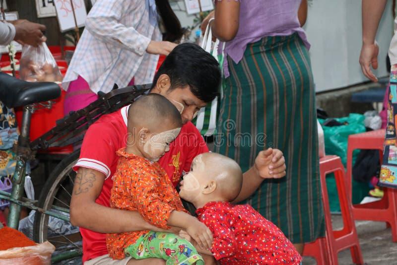 Padre de Myanmese y 2 niños con el polvo de Myanmar del thanakha en sus caras, jugando la diversión feliz junto en el mercado foto de archivo libre de regalías