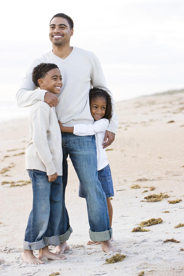 Padre del African-American e due bambini sulla spiaggia fotografia stock