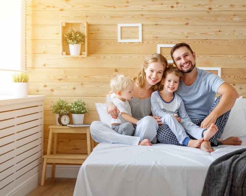 Padre della madre della famiglia e bambini felici derivato e figlio a letto fotografia stock