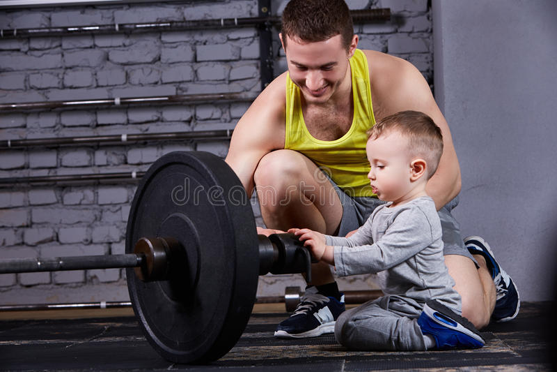 Padre deportivo joven que muestra las pesas de gimnasia para su pequeño hijo y que sonríe contra la pared de ladrillo en el gimna fotos de archivo libres de regalías