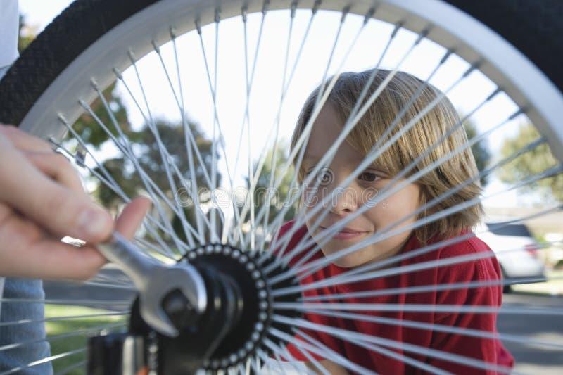 Padre di sorveglianza Fix Bicycle Tyre del ragazzo immagini stock
