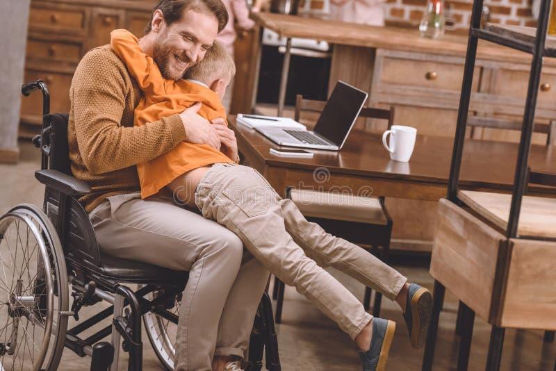 padre discapacitado feliz en la silla de ruedas que abraza con el pequeño hijo lindo fotos de archivo