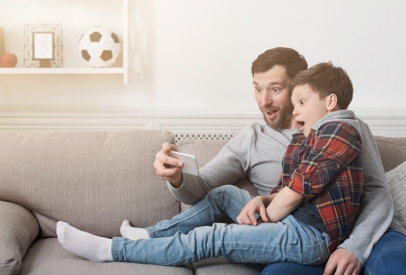 Padre divertente e suo il figlio che prendono selfie a casa fotografia stock libera da diritti
