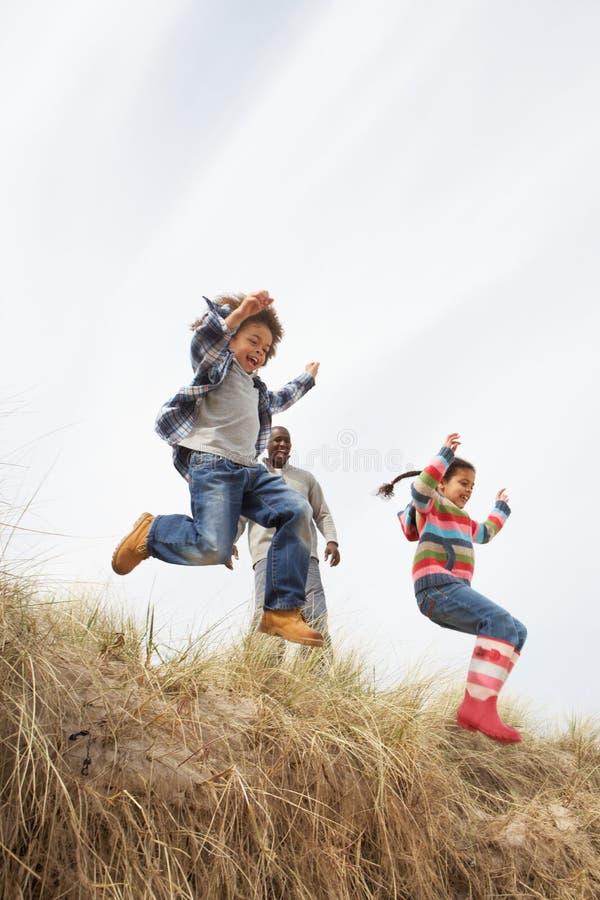 Padre e bambini che hanno divertimento in dune di sabbia fotografia stock libera da diritti