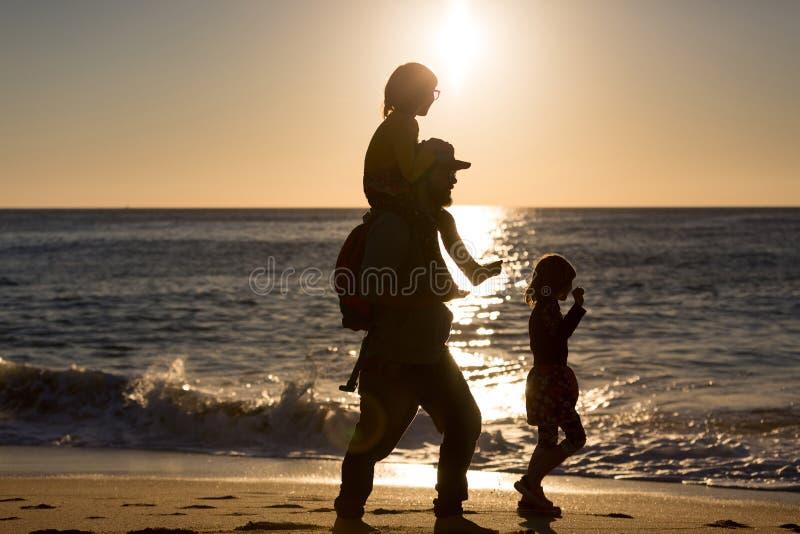 Padre e bambini sulla spiaggia durante il tramonto fotografie stock libere da diritti