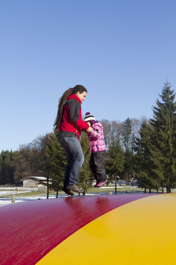 Padre e bambino che saltano sul trampolino fotografia stock libera da diritti