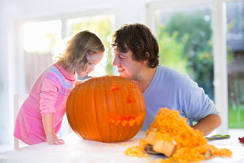 Padre e bambino che scolpiscono zucca per Halloween fotografia stock