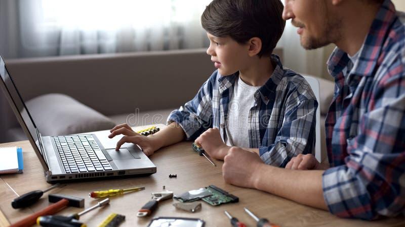 Padre e bambino che si siedono alla tavola, cercante insieme video esercitazione del PC sul computer portatile fotografia stock libera da diritti