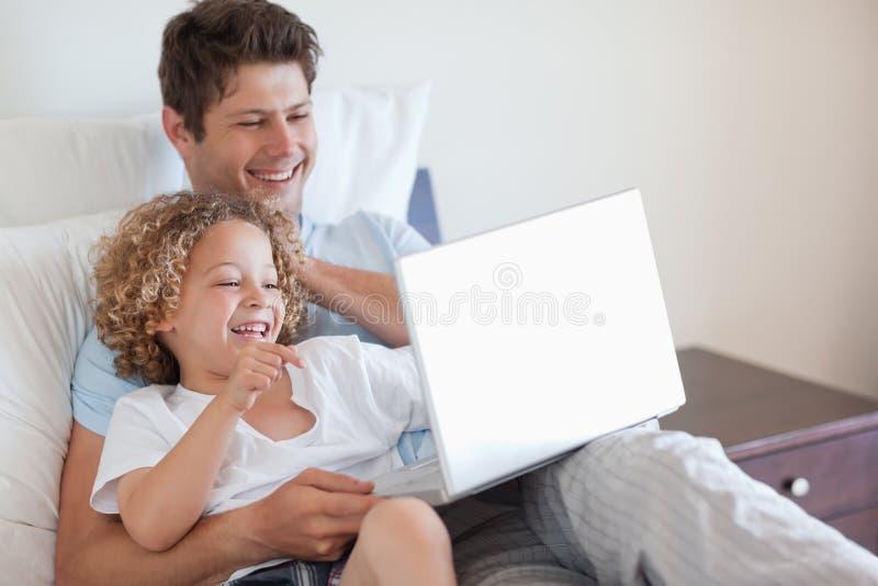 Padre e bambino che utilizza computer portatile nella base immagine stock
