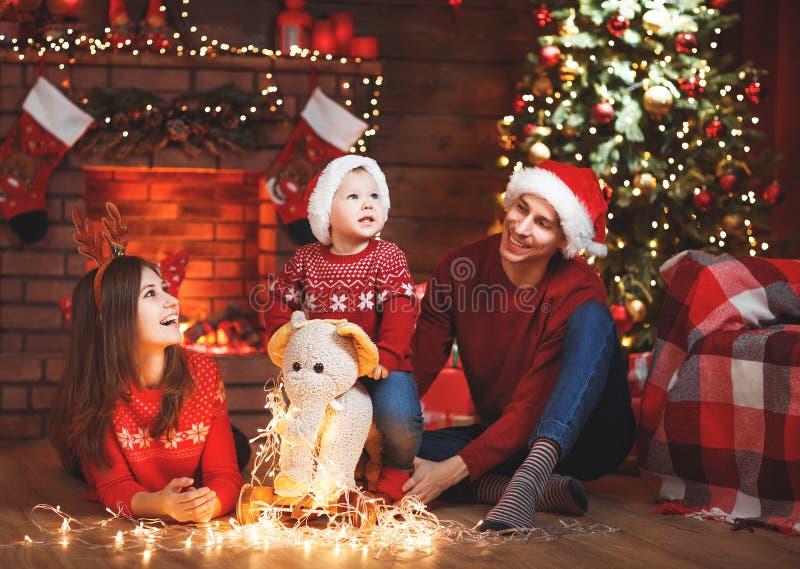 Padre e bambino felici della madre della famiglia all'albero di Natale a casa fotografia stock libera da diritti