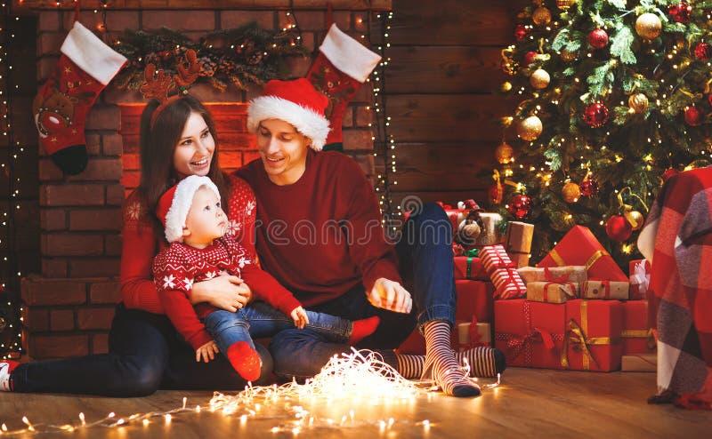 Padre e bambino felici della madre della famiglia all'albero di Natale a casa immagini stock