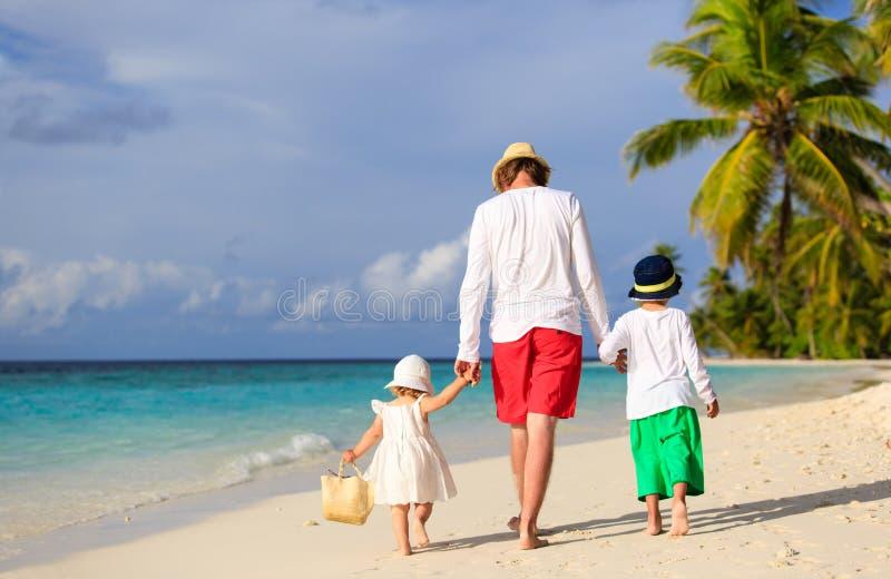 Padre e due bambini che camminano sulla spiaggia fotografia stock