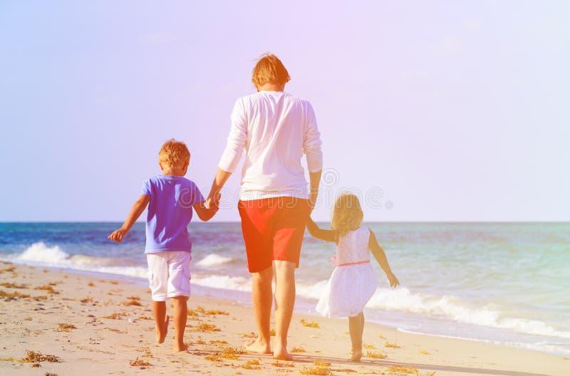 Padre e due bambini che camminano sulla spiaggia fotografie stock