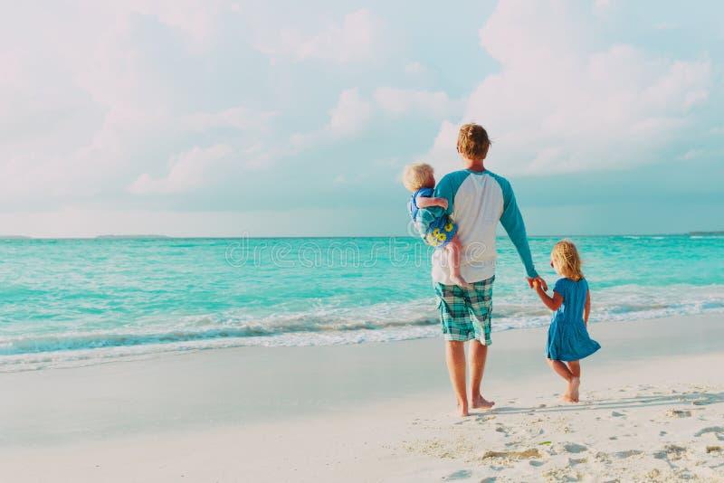 Padre e due poca passeggiata della figlia sulla spiaggia fotografia stock libera da diritti