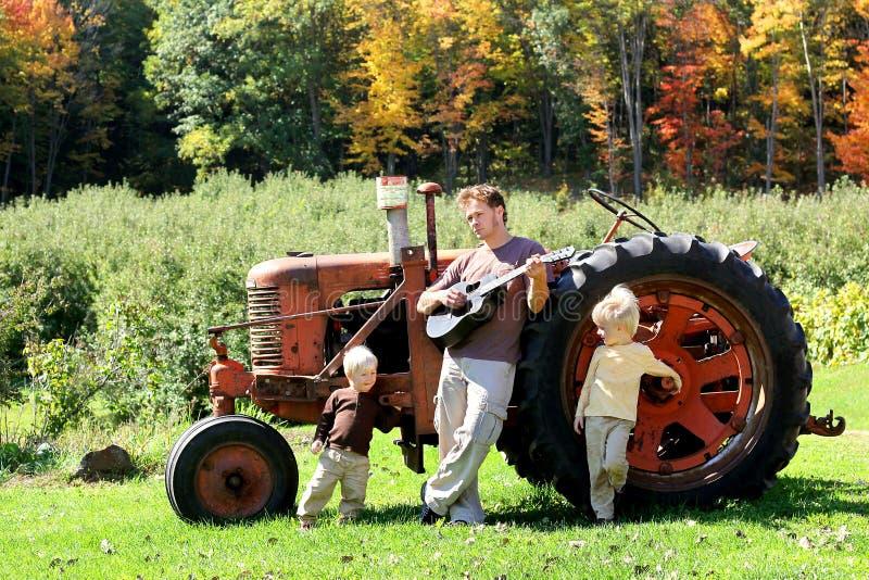 Padre e figli che giocano chitarra in vecchio trattore agricolo immagini stock libere da diritti