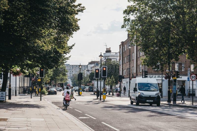Padre e figlia che ciclano su una via in Pimlico, Londra, Regno Unito, un giorno di estate luminoso fotografia stock