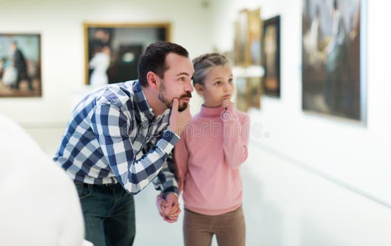 Padre e figlia che esaminano le esposizioni fotografie stock