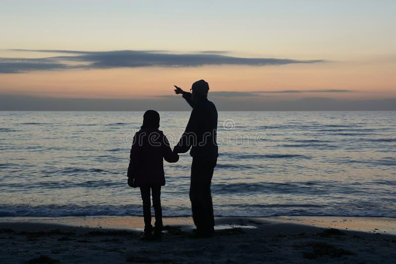 Padre e figlia che esaminano mare fotografie stock