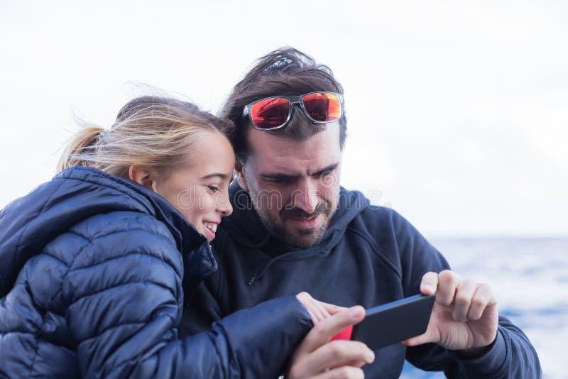 Padre e figlia che esaminano telefono fotografia stock libera da diritti