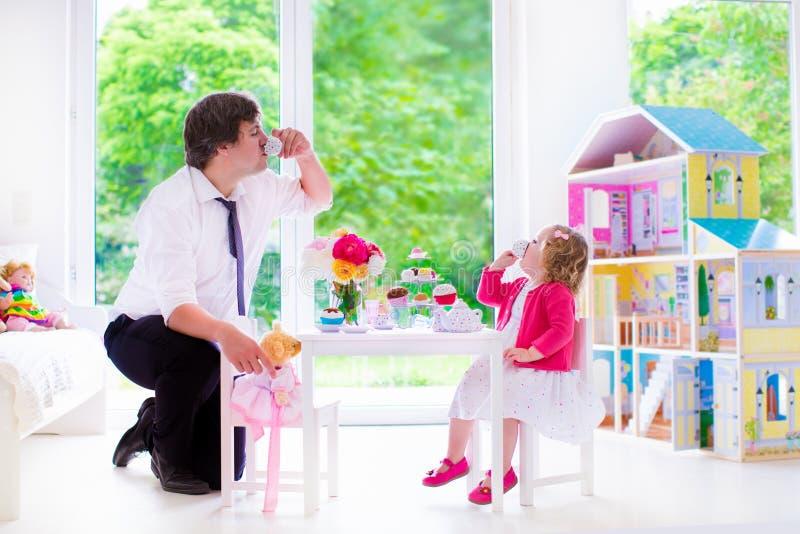 Padre e figlia che giocano il ricevimento pomeridiano della bambola fotografie stock libere da diritti