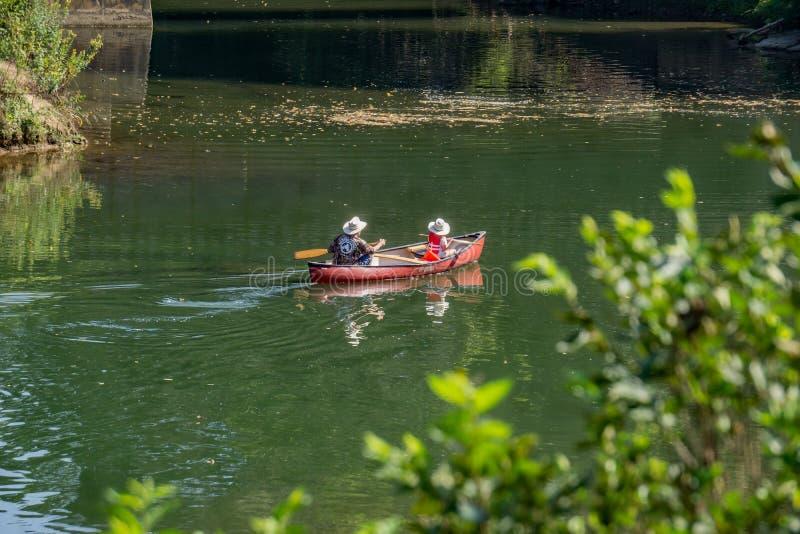 Padre e figlia che godono di un giorno sul fiume fotografia stock