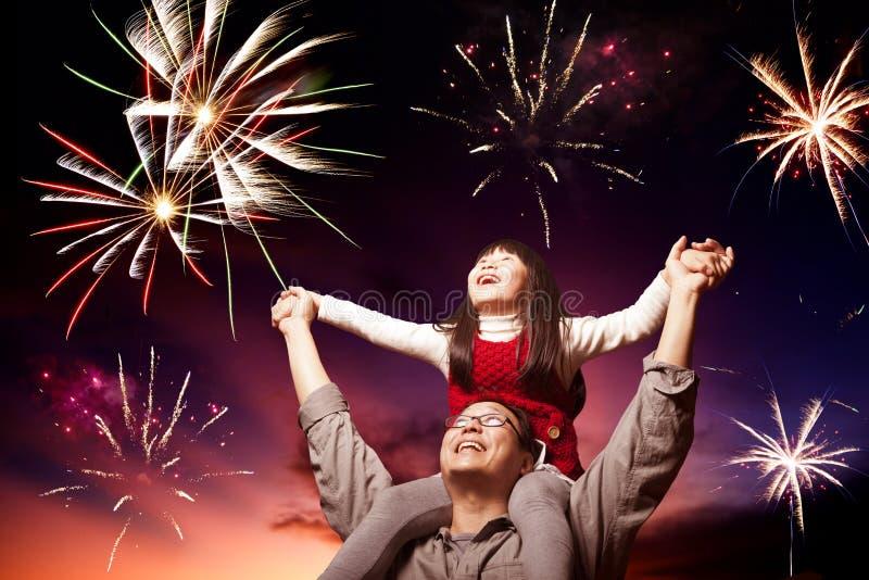 Padre e figlia che guardano i fuochi d'artificio fotografia stock
