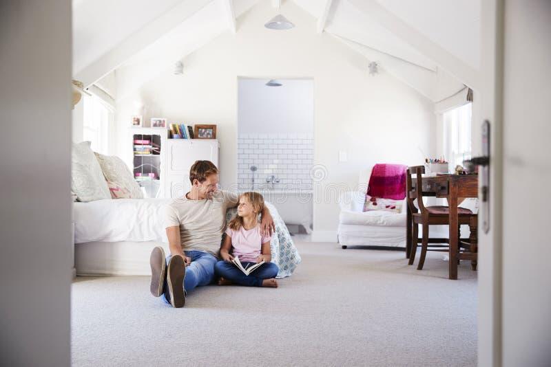 Padre e figlia che leggono insieme un libro nella sua camera da letto immagini stock libere da diritti