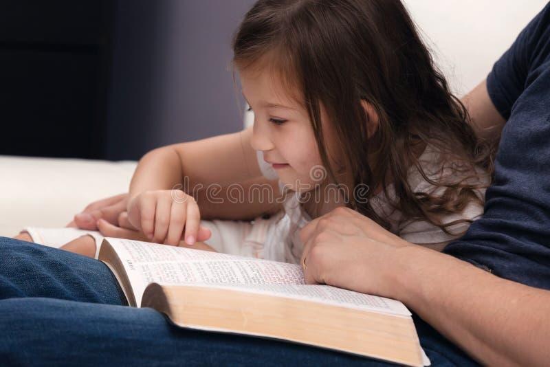 Padre e figlia che leggono la bibbia fotografia stock libera da diritti