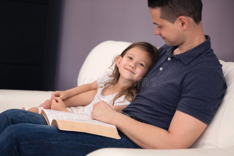 Padre e figlia che leggono la bibbia fotografie stock