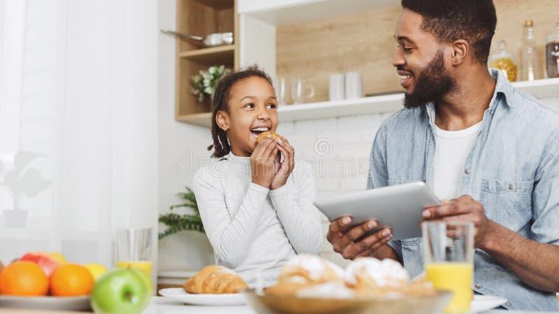Padre e figlia che mangiano prima colazione immagini stock