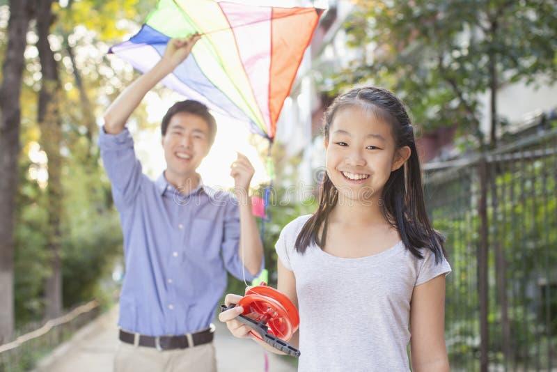 Padre e figlia che pilotano un aquilone fotografia stock libera da diritti
